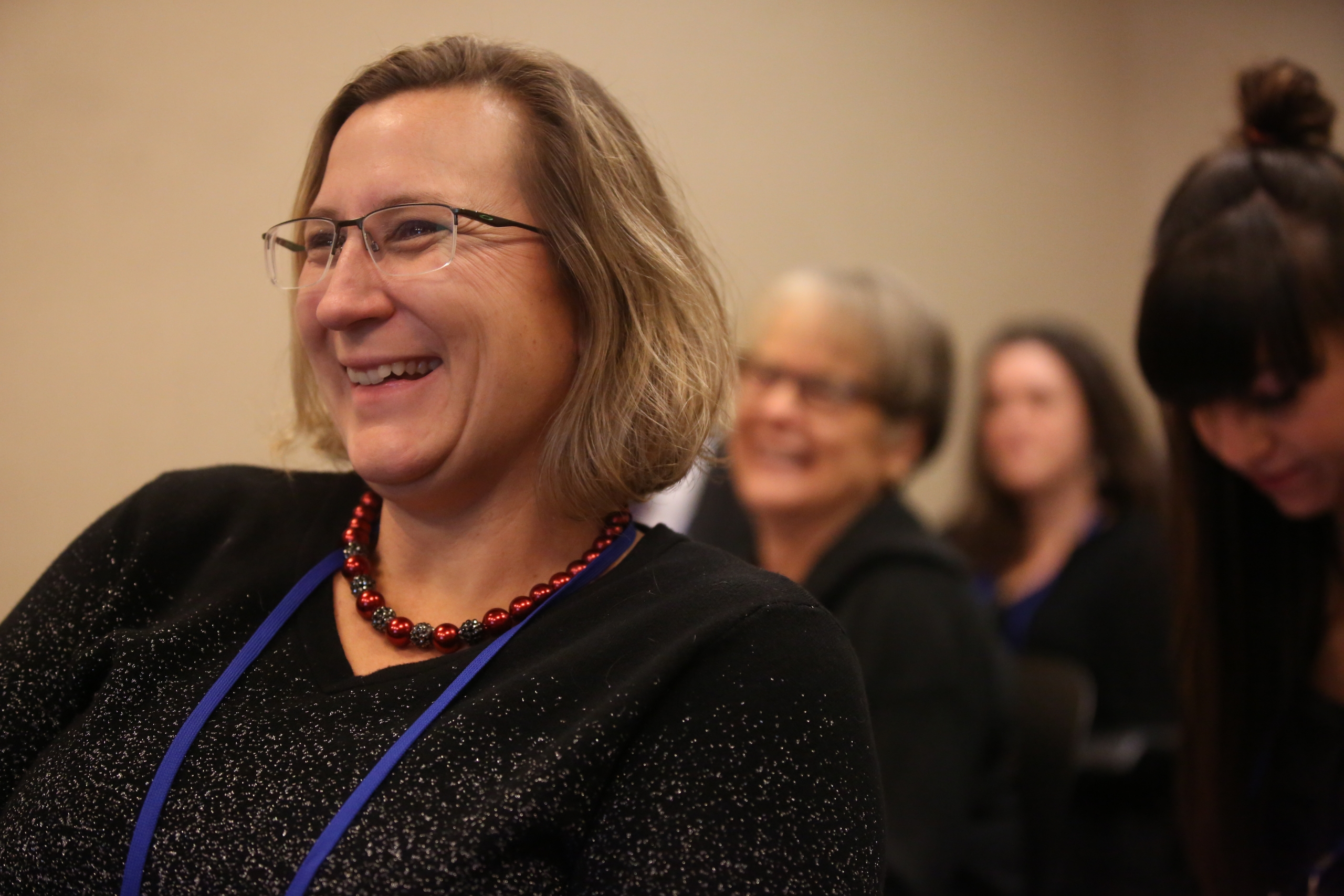 A woman smiles during a breakout session