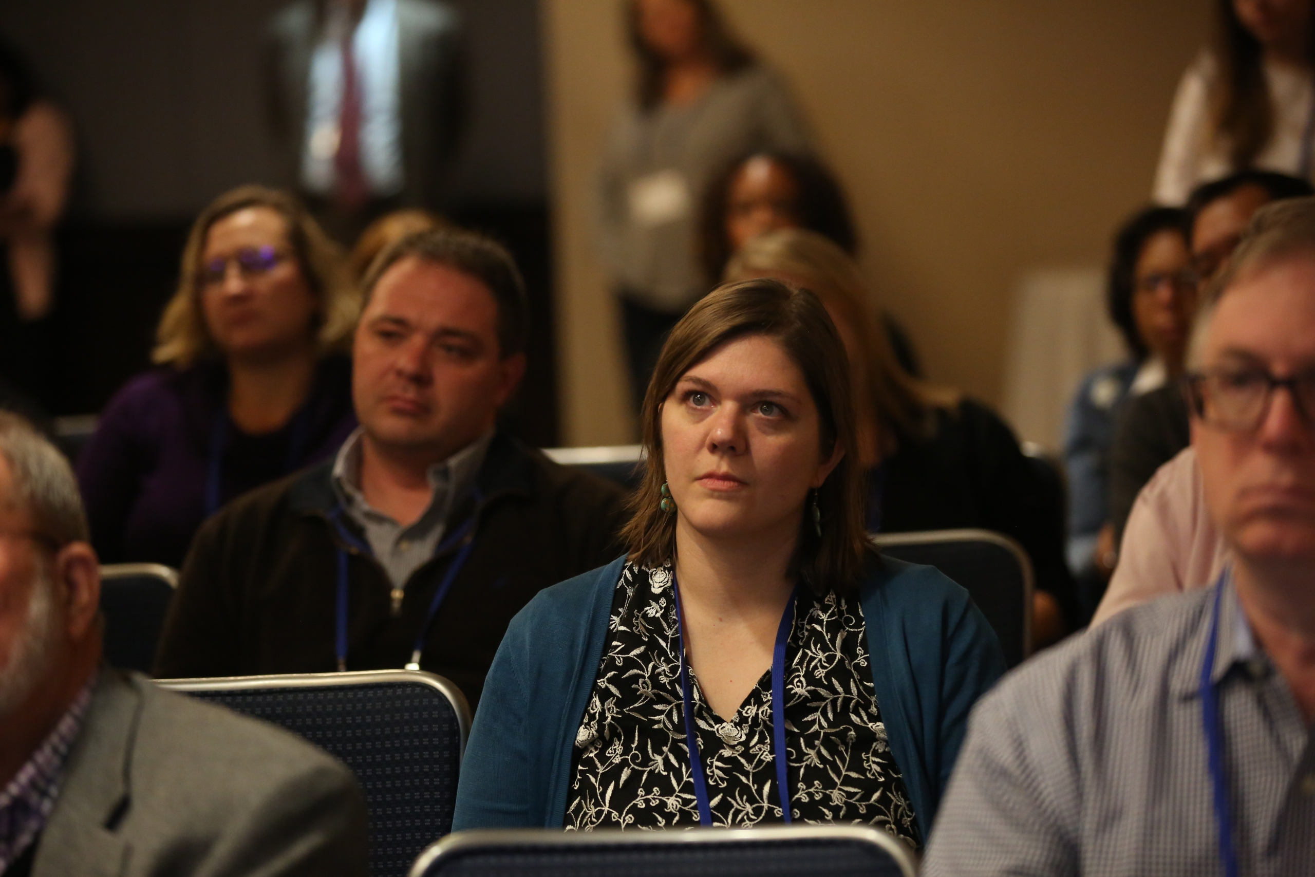 A woman listens in a crowded breakout session