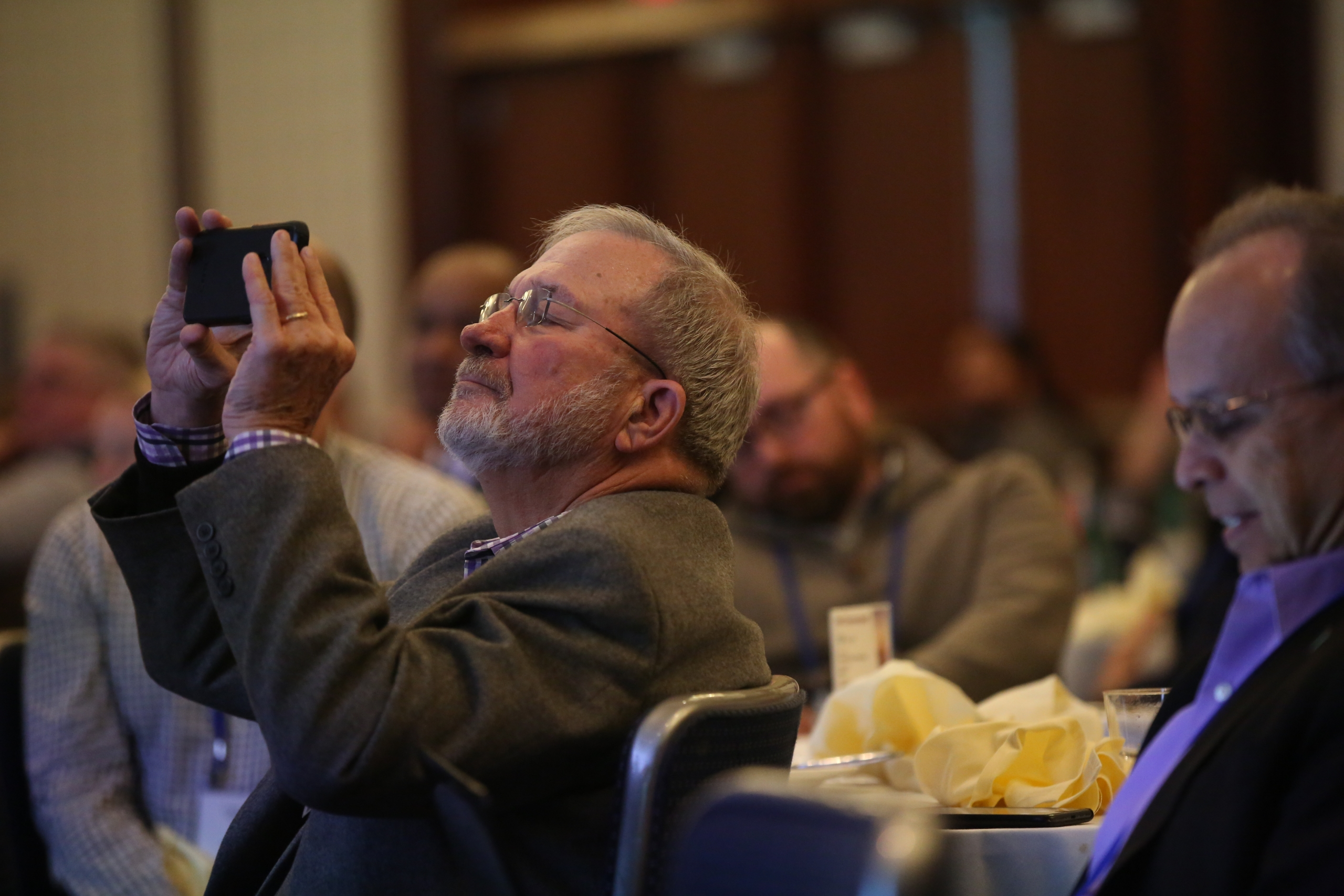A man uses his phone to snaps a photo in the middle of a presentation