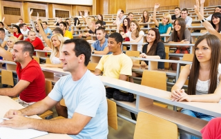 College students in lecture hall with raised hands
