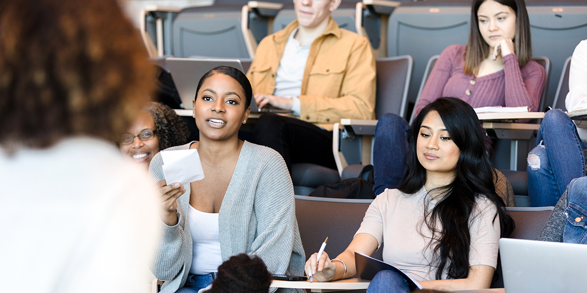 As an unrecognizable female college professor gives a lecture, a mid adult female student asks a question.