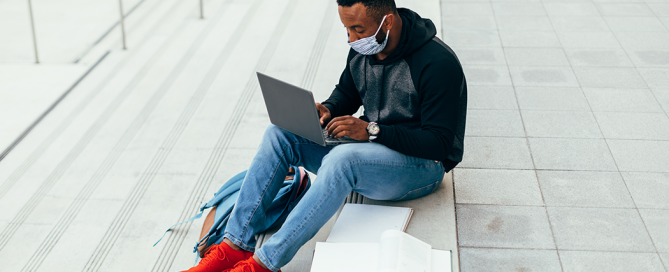 A college student wearing a mask sits with open books and a laptop