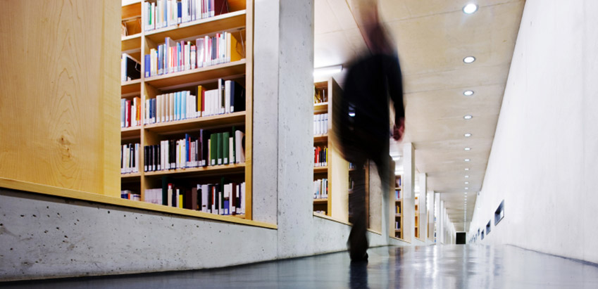 Student walking down the library corridor