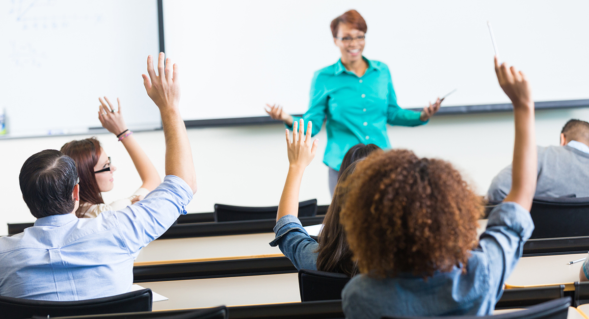 Students raising hands to ask question in lecture hall classroom