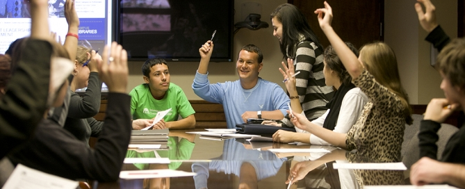 Students sitting at a conference table, raising hands.