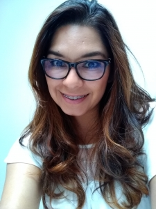 A woman with dark hair, glasses, and braces smiles for a selfie.