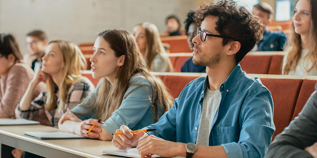 Students listen to an instructor in a classroom. The students, who appear college-aged, have notebooks and pencils.