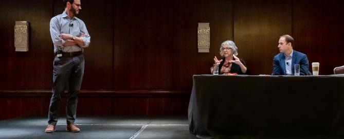 Evan Weissman stands while Elisabeth Barnett and Alexander Mayer sit on stage during a presentation