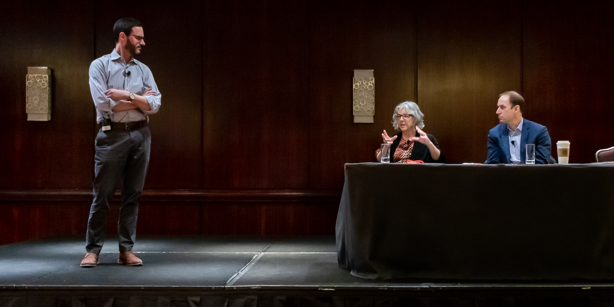 Evan Weissman stands while Elisabeth Barnett and Alexander Mayer sit on stage during a presentation
