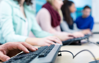 Anonymous students type in a computer lab