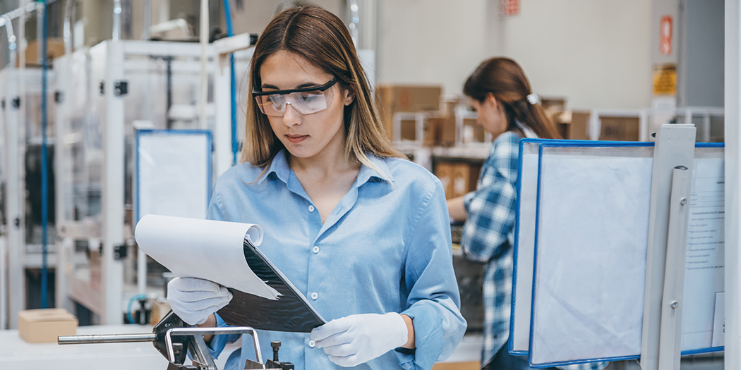 A factory employee in safety goggles examines a clipboard