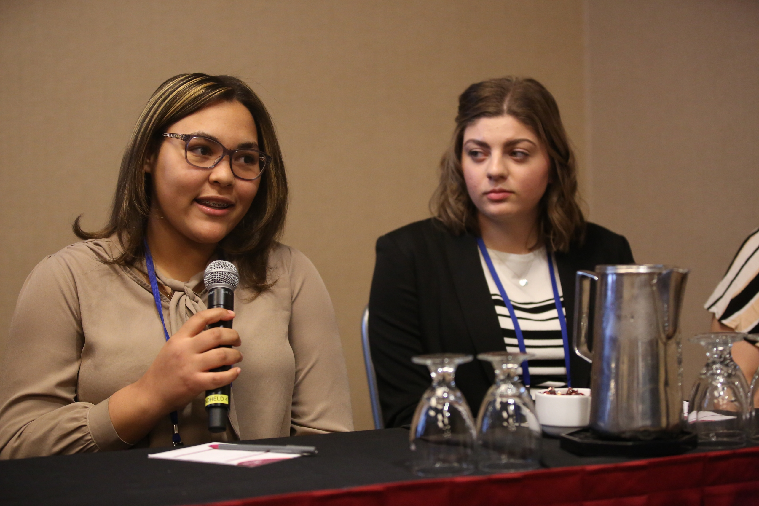 Two women sit behind a table. One holds a microphone