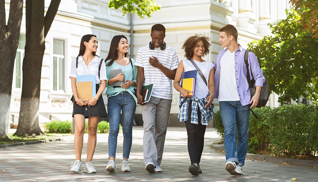 A group of students walk around campus together