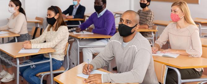 Students in mask sit at desks