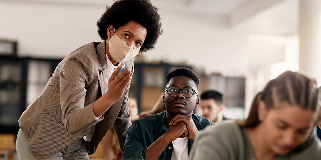 A professor wearing a mask helps a student in class